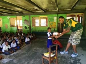 Kaliova Selei presents Footys4All to young Fijian